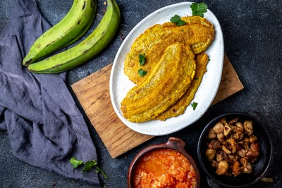 Colombian Patacon or toston, fried and flattened whole green plantain banana on white plate