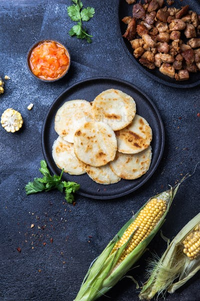 Colombian Maize Arepas and Fried Pork Chicharron and Tomato Sauce. Top View. Black Background.