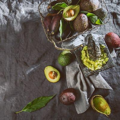 Guacamole Sauce and Fresh Avocado on Gray Linen Tablecloth
