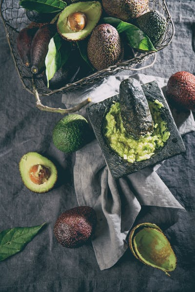 Mexican Guacamole Sauce in Stone Mortar, Full Basket with Avocado on Linen Tablecloth