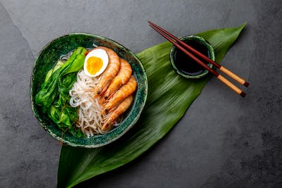 Rice Noodles with Shrimps, Egg, Pok choy Cabbage in Green Bowl, Gray Background. Top View.