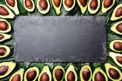 Avocado Frame Made From Avocado and Avocado Tree Leaves Around Black Slate Board
