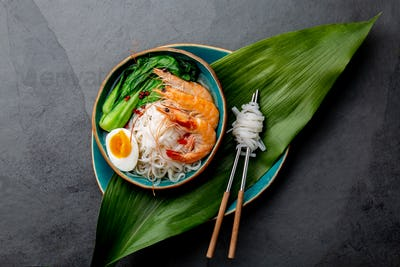 Rice Noodles With Shrimps, Egg, Pok Choy Cabbage in Blue Bowl, Gray Background. Top View.