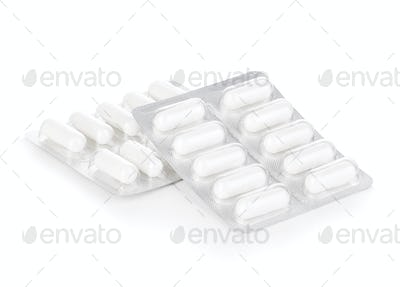 Capsule pills in blister pack close-up isolated on a white background.