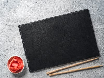 Empty slate with chopsticks and pickled ginger