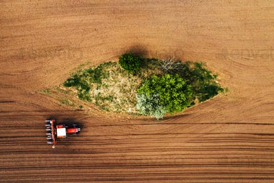 Top view of tractor with seeder from drone pov