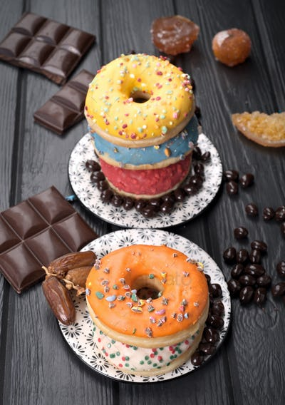 colorful glazed donuts on black wooden table