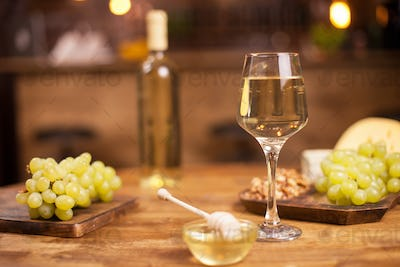 Close up of a glass of wine next to a bowl of tasty golden honey on a wooden table in a vintage pub