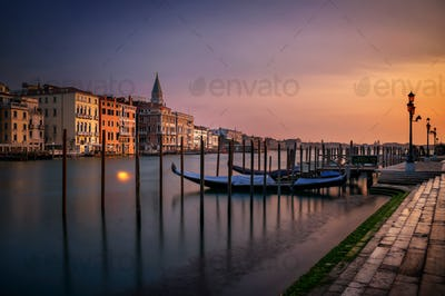 San Marco Campanile with gondolas at Grand Canal during calm sunrise, Venice, Italy, Europe.