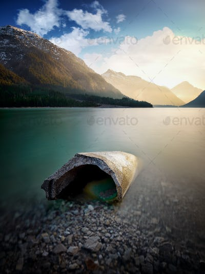 Landscape of Plansee and Alps mountains. Concrete block lying in lake, Tyrol, Austria