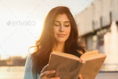 Young woman reading book outdoors, walking on city street