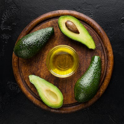 Sliced and whole avocadoes and oil