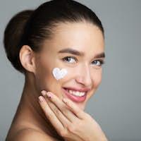 Beauty Skin Care. Cream In Heart Shape On Female Cheek