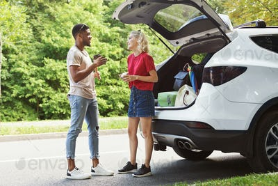 Multicultural couple standing near car