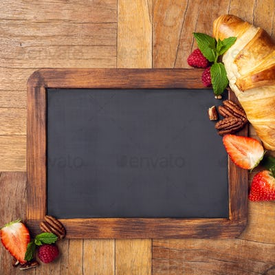 Black chalkboard with croissant and berries