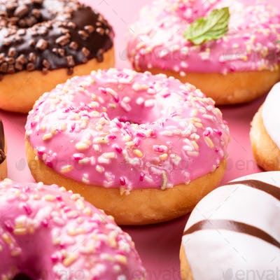 Colorful donuts on rose background