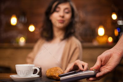 Photo of attractive woman paying with mobile phone using wireless payment on a coffee shop