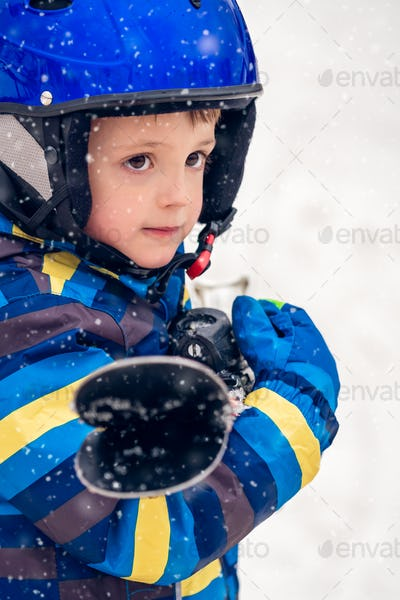 Portrait of a little boy holding his skis