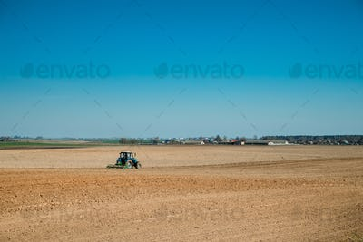 Tractor Plowing Field In Spring Season. Beginning Of Agricultura