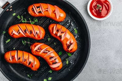 Grilled sausages in cast iron pan.
