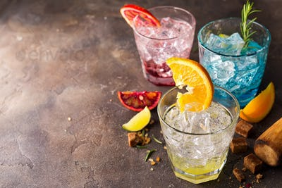 Set of colorful cocktails with fruits and herbs, brown sugar on stone background