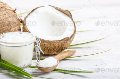 Coconut oil in airtight glass jar spoon and shell pieces on whit