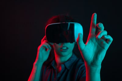 Cheerful beautiful young woman entertained with virtual reality helmet in studio and colorful