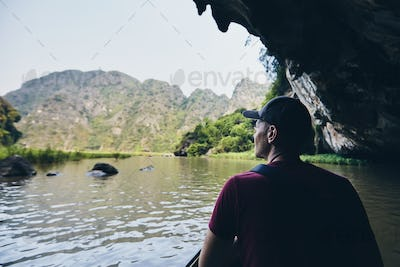 Man on boat floating through to cave