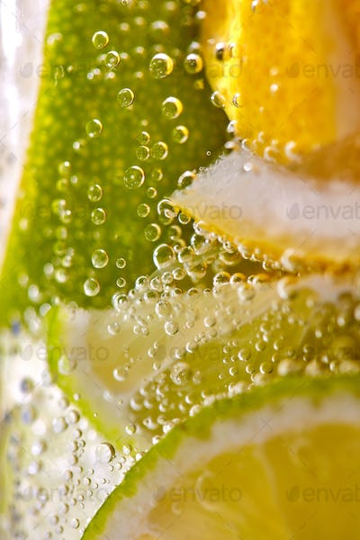 Macro photo of freshly made lemonade with pieces of lime, lemon and bubbles in a glass. Summer
