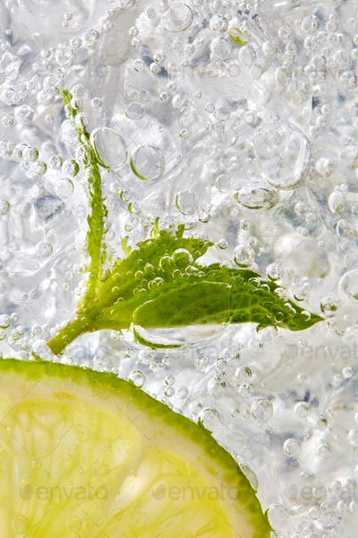 Fresh mint leaf and a slice of lime with bubbles in a glass with ice. Macro photo of refreshing