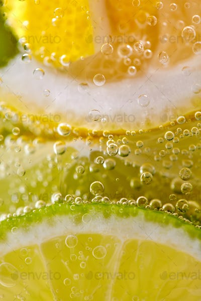 Ripe sliced pieces of lemon and lime in a glass with water and bubbles. Macro photo of summer