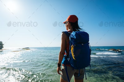 Hiker looking at the beautiful sunrise view at seaside
