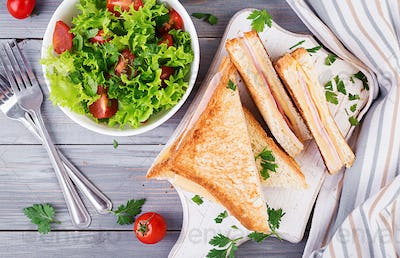 Club sandwich panini with ham, cheese and salad. Top view. Tasty breakfast