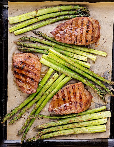 Barbecue grilled beef steak meat with asparagus and herbs. Top view