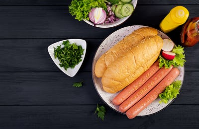 Ingredients for hot dog with  sausage, cucumber, radish and lettuce