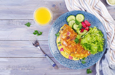 Breakfast. Omelette with radish, red onion and fresh salad on blue plate.