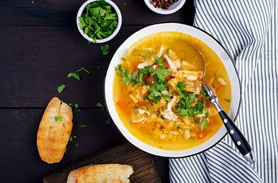 Red lentil soup with chicken meat and vegetables close-up on the table. Healthy food. Top view