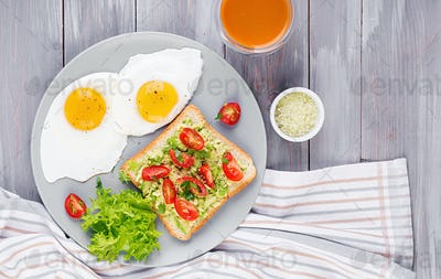 Breakfast. Fried egg, vegetable salad and a grilled avocado sandwich on a grey background. Top view