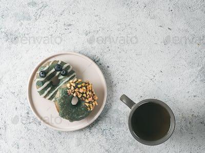 Vegan donuts topped spirulina glaze and tea