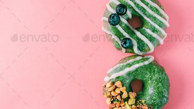 Donut topped matcha tea glaze on pink