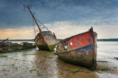 Old boat wrecks under a stormy sky