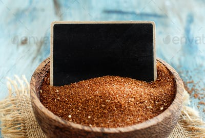 Raw teff grain with a small chalkboard