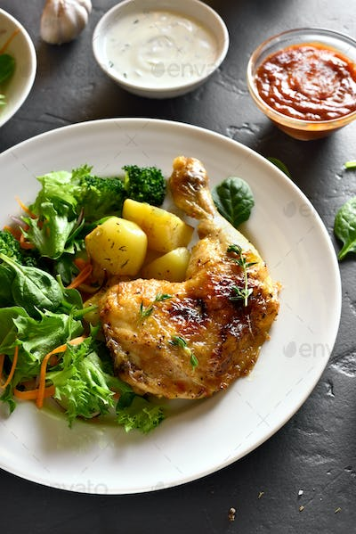 Roasted chicken leg with potato and green salad