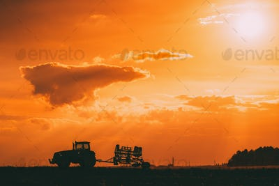 Tractor Rides On Countryside Road. Beginning Of Agricultural Spr