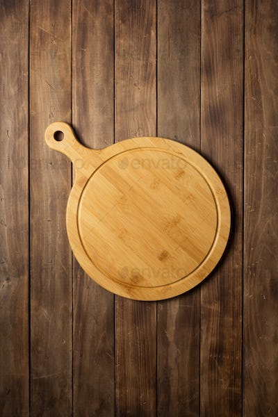 pizza cutting board at wooden plank board background