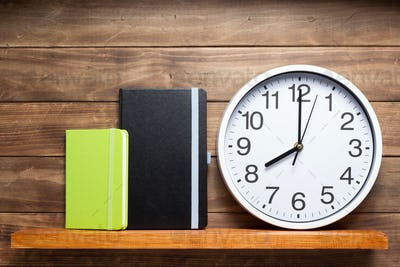 wall clock and book at shelf on wooden background