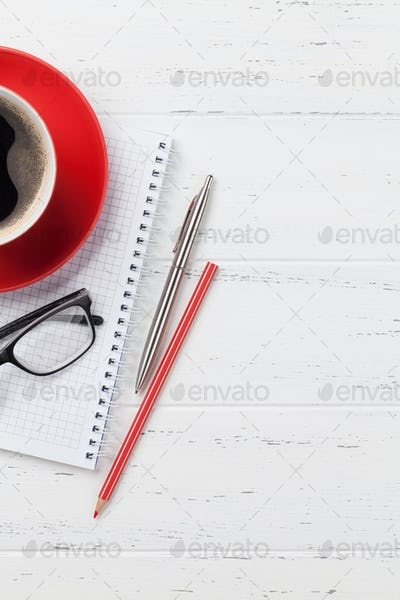 Office desk with coffee cup and supplies