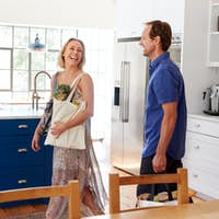 Mature Couple Returning Home From Shopping Trip Carrying Grocery Bags Through Kitchen