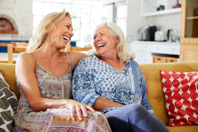 Smiling Mother With Adult Daughter Relaxing On Sofa At Home