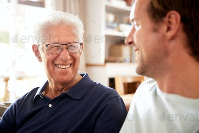 Smiling Father With Adult Son Relaxing On Sofa At Home